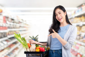 Asian woman with shopping basket full of groceries in supermarke