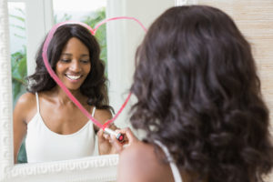 Beautiful young woman drawing big heart on mirror with lipstick