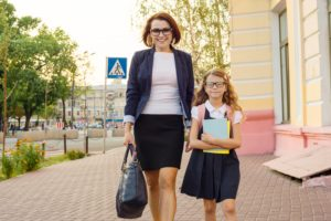 Mother businesswoman takes the child to school
