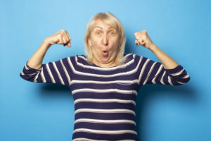 Portrait of an old friendly woman with a surprised face in a casual t-shirt makes a bodybuilder gesture on an isolated blue background. Emotional face. Gesture strength, power, good health.